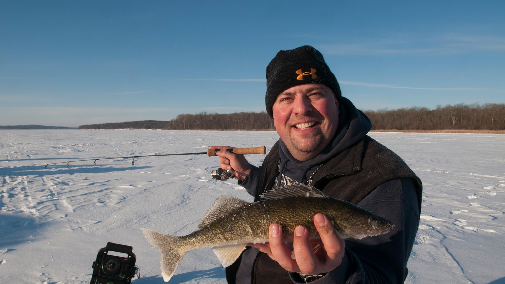 Man catching a fish while ice fishing on Leech Lake