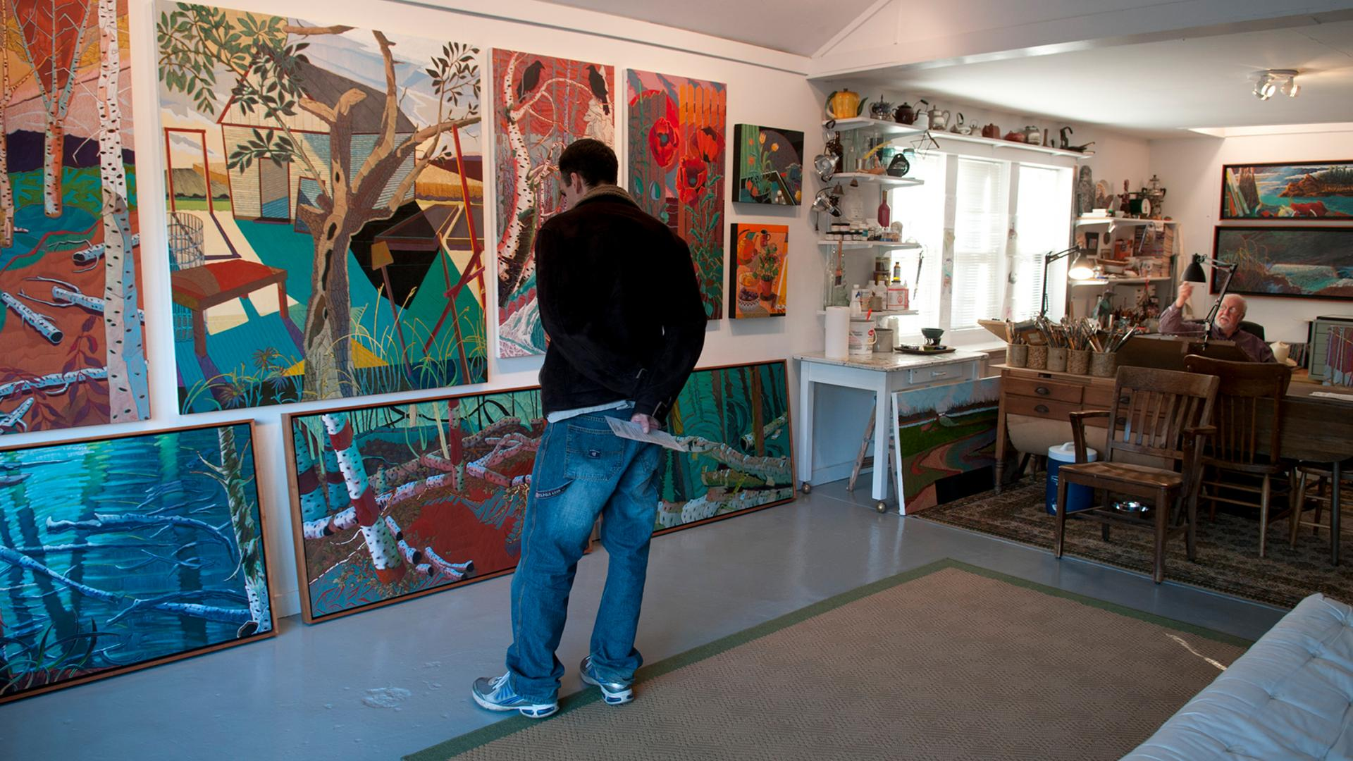 A man looks at colorful artwork in Marley Kaul art studio in Bemidji