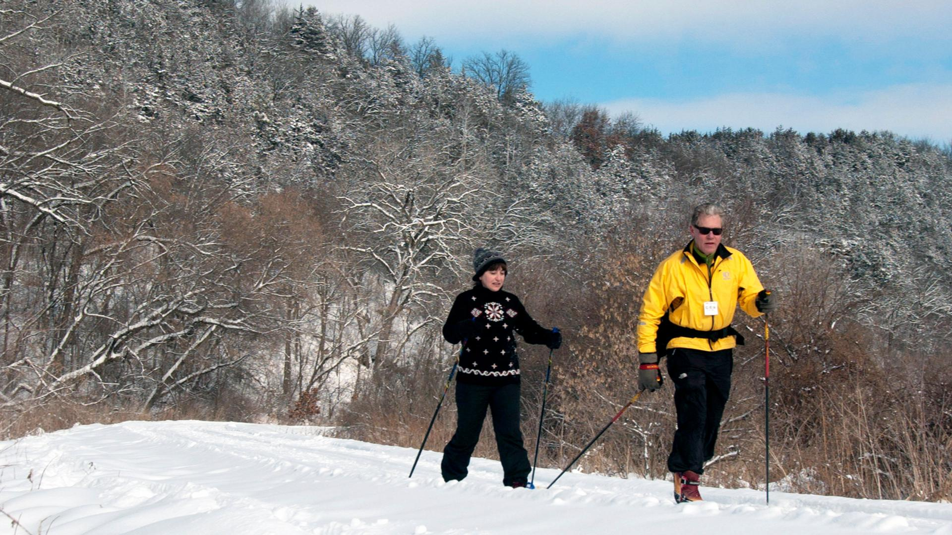 Couple cross country skiing on the Root River Trail in the Lanesboro area