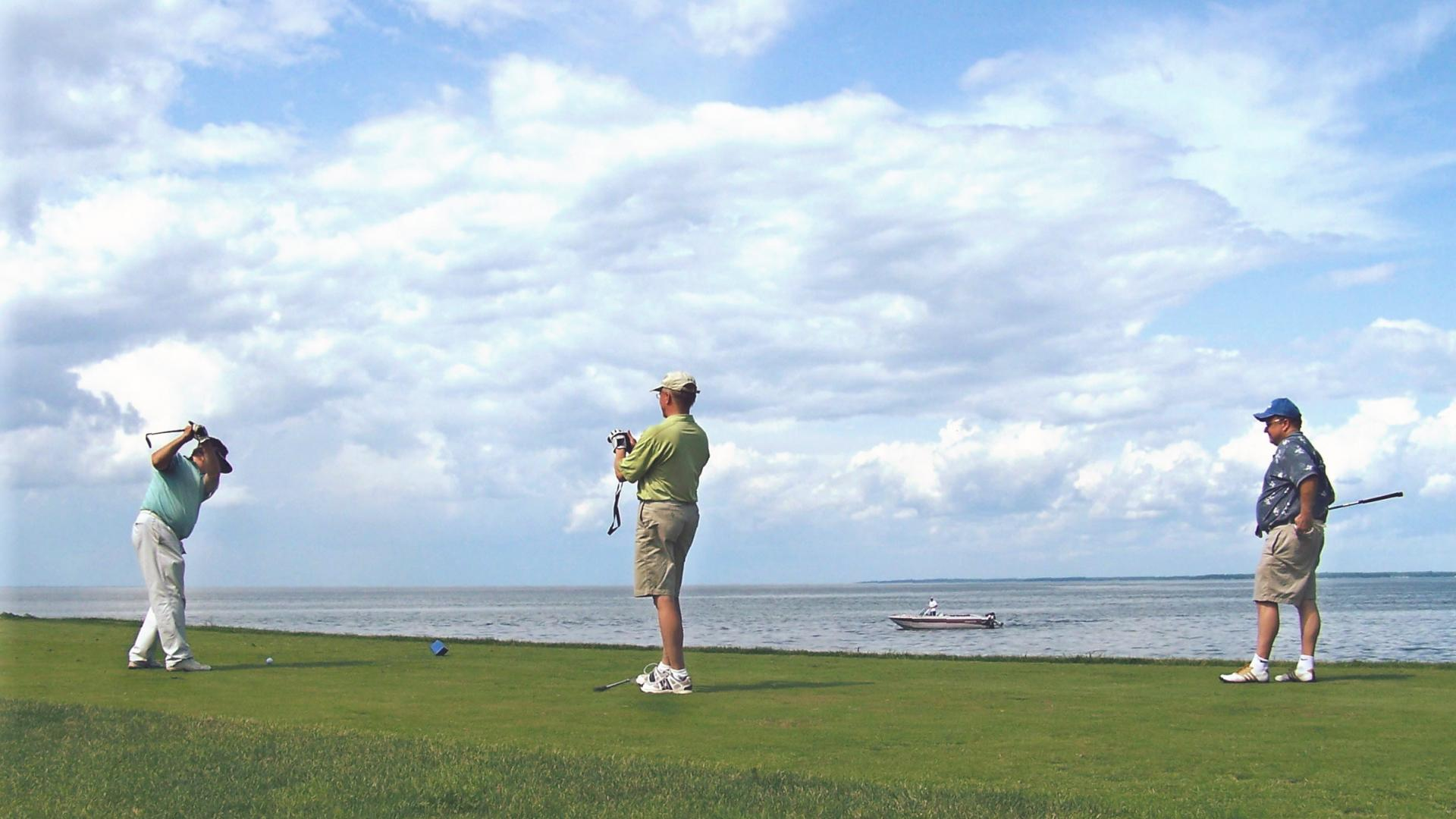 Three golfers at Izatys with Lake Mille Lacs in background