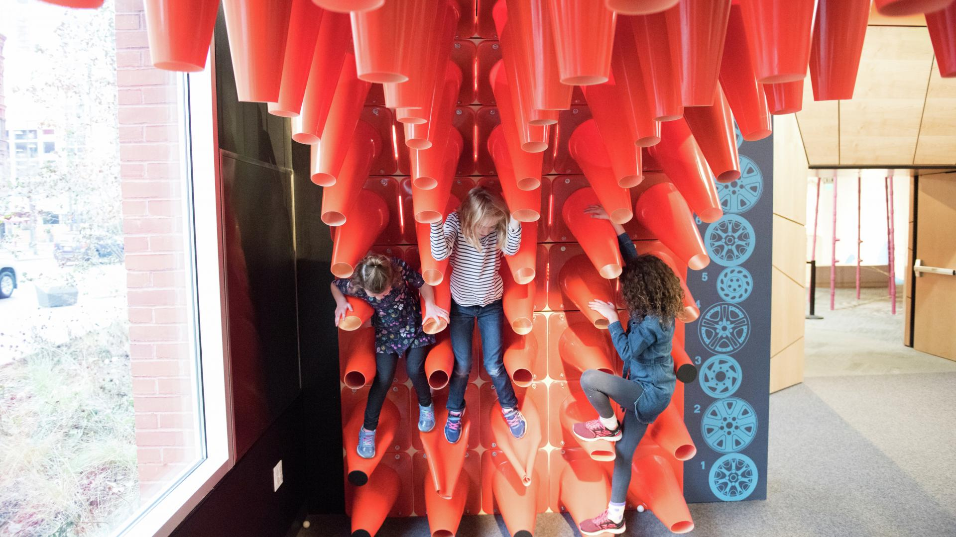Kids climb on interactive safety cone exhibit