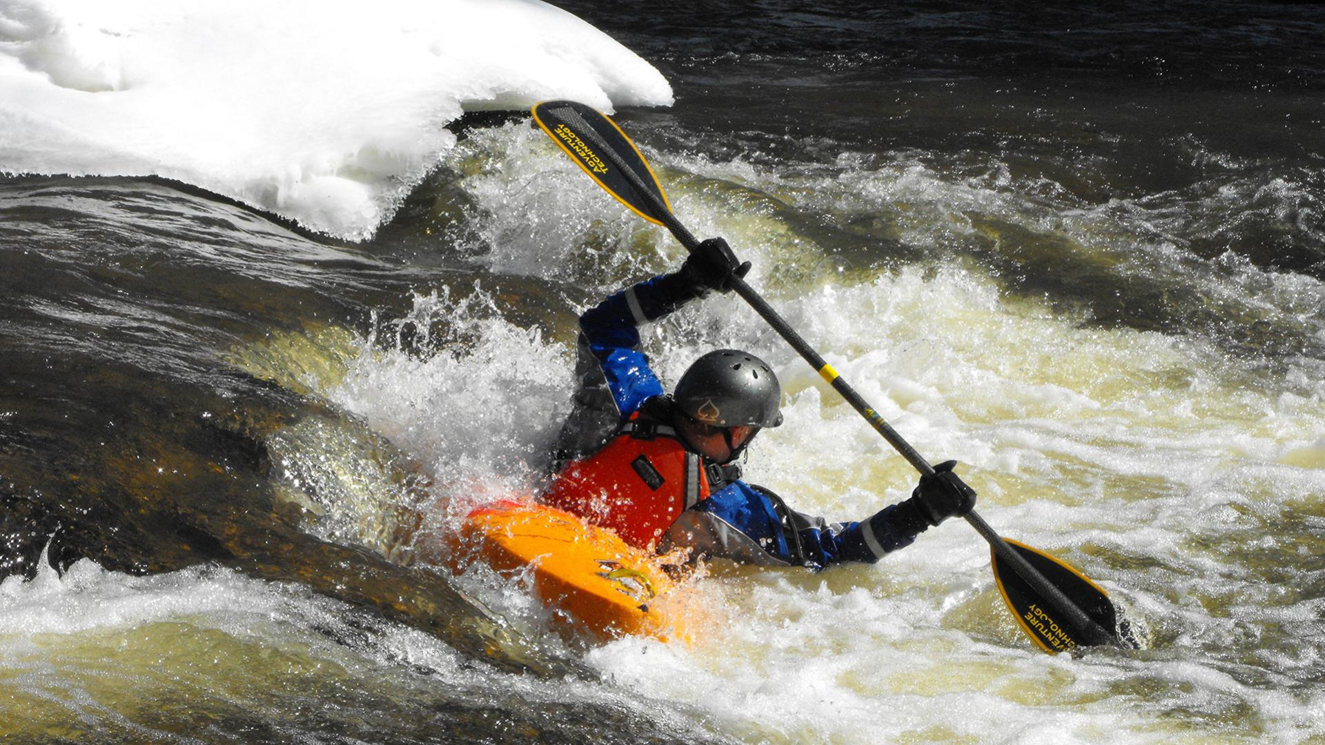 A kayaker takes advantage of the winter white caps as he navigates down the river