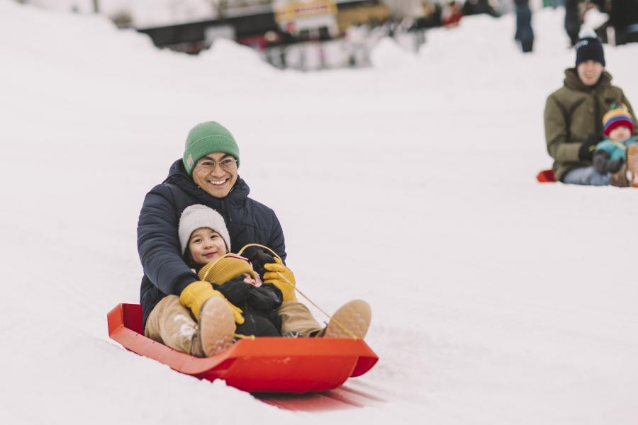 Dad and son on a sled at the Saint Paul Winter Carnival