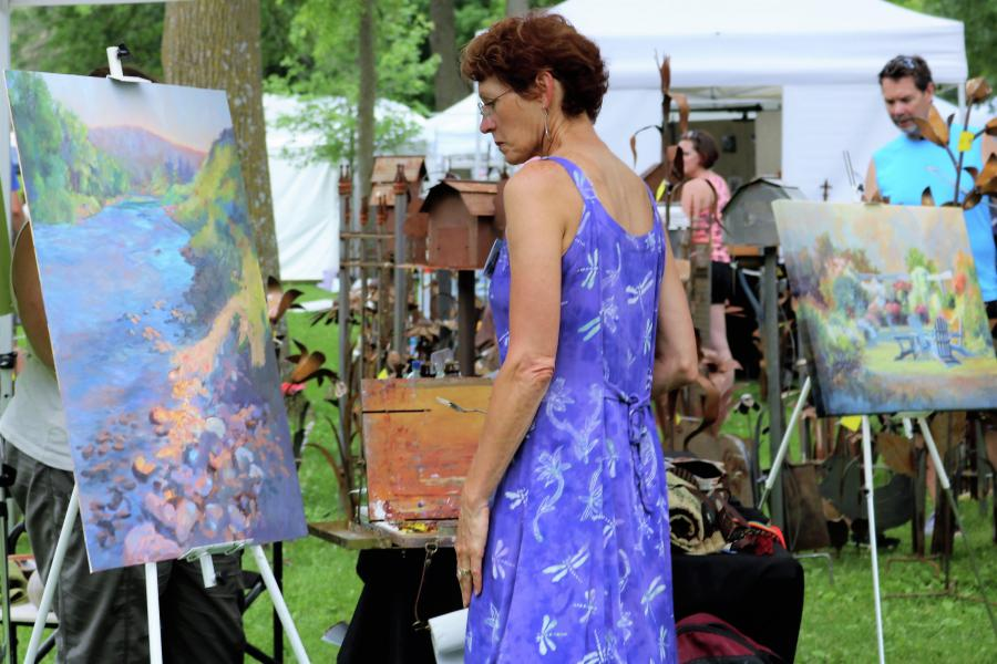 Woman looking at painting at Art in the Park