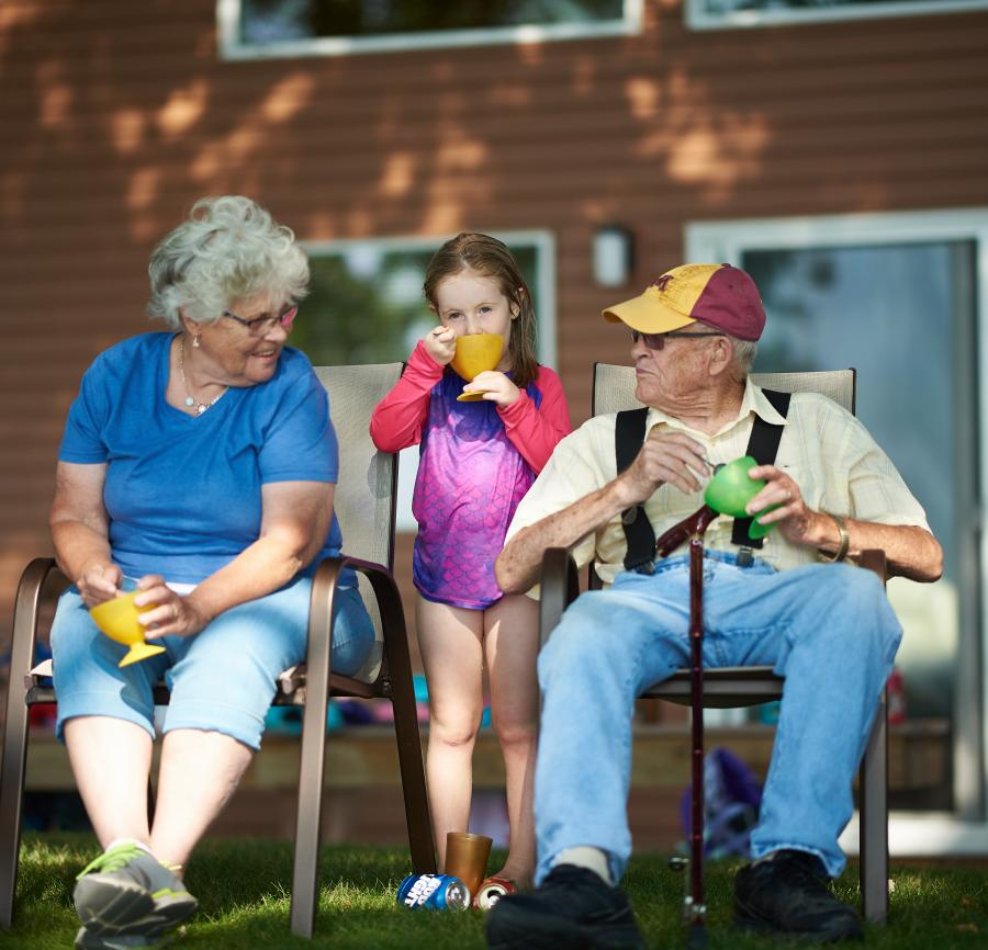 Grandparents and granddaughter eat ice cream outside