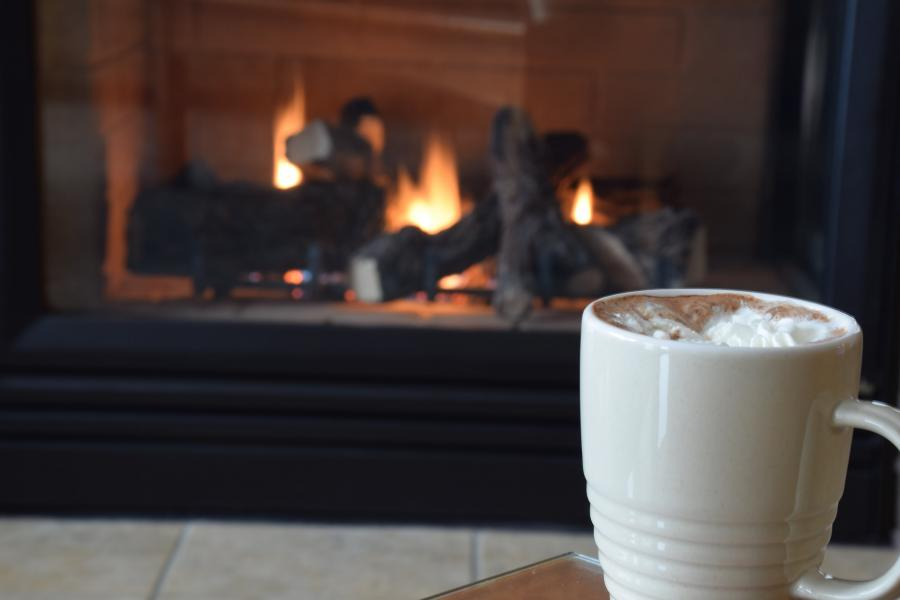 A cup of hot cocoa in front of a fireplace