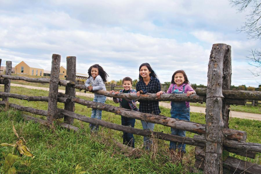 Kids pose on log fence at Oliver Kelley Farm
