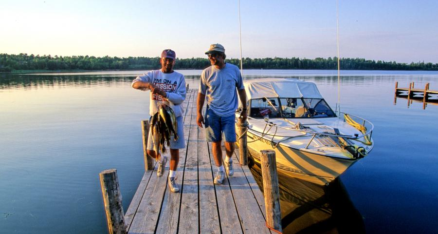 Lake of the Woods holding stringer of fish on dock Sportsman's Oak Island Resort