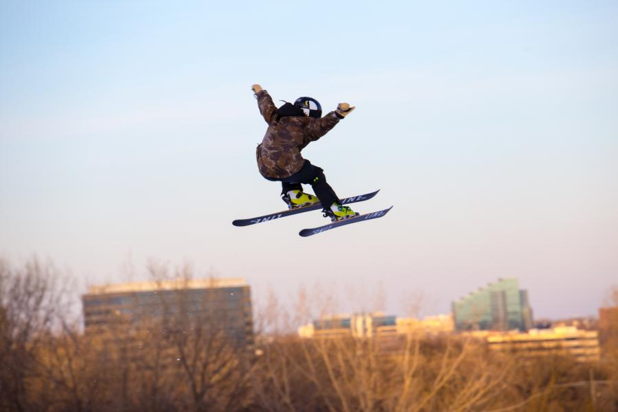 Skier jumping with buildings behind at Hyland Hills
