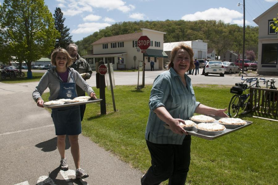 Women carrying trays of pies in Whalan