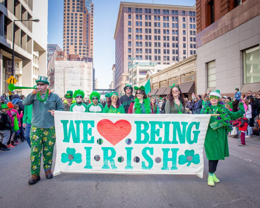 "Parade-goers holding a ""we love being Irish"" banner"