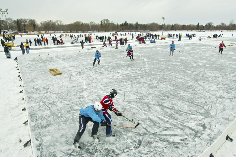Pond hockey players chase after the puck