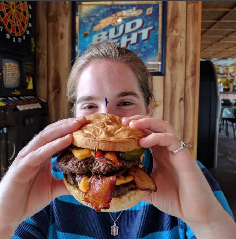 woman holding up a bacon cheeseburger