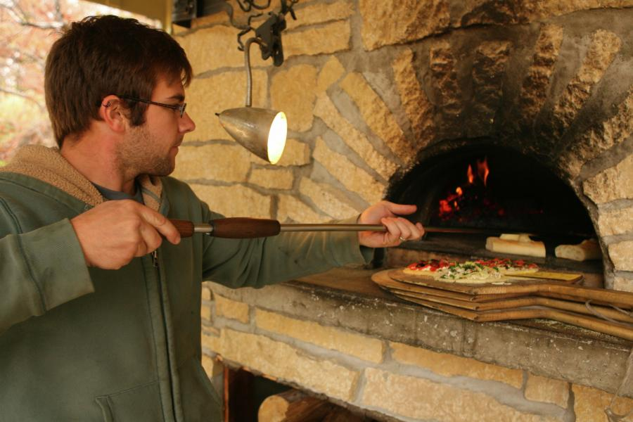 Man tending a wood-fired pizza oven