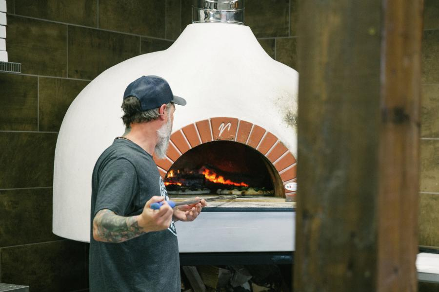 Man tends wood-fired pizza oven