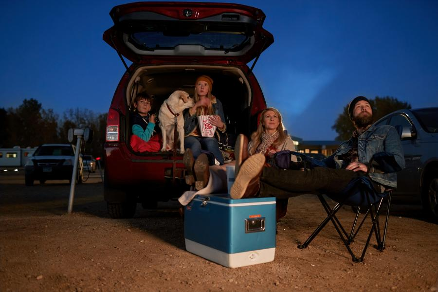 Family watching a drive-in movie