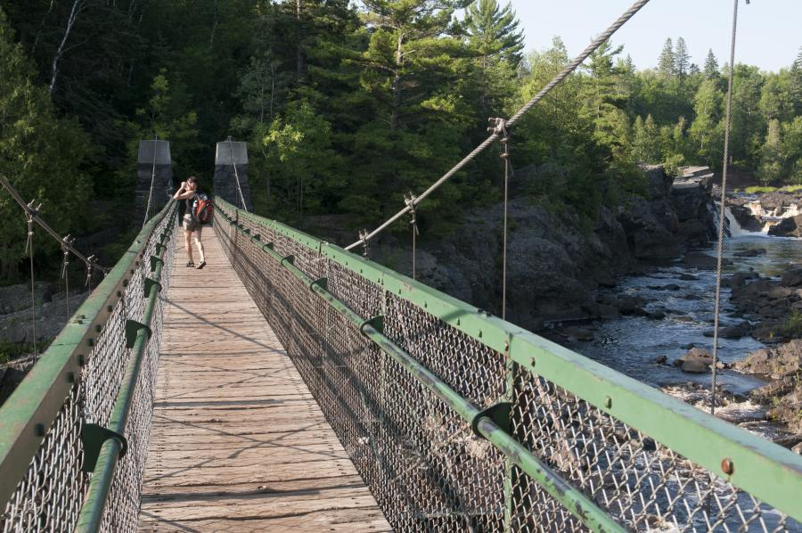 Hiker on the suspension bridge at Jay Cooke State Park