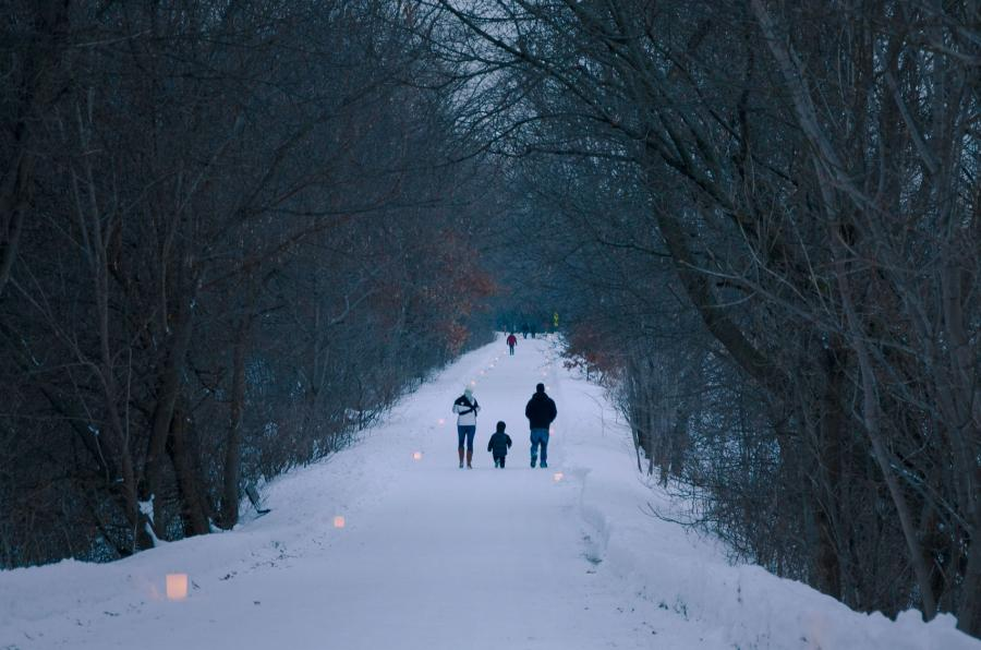 Family on a winter walk along the luminary-lit Gateway State Trail