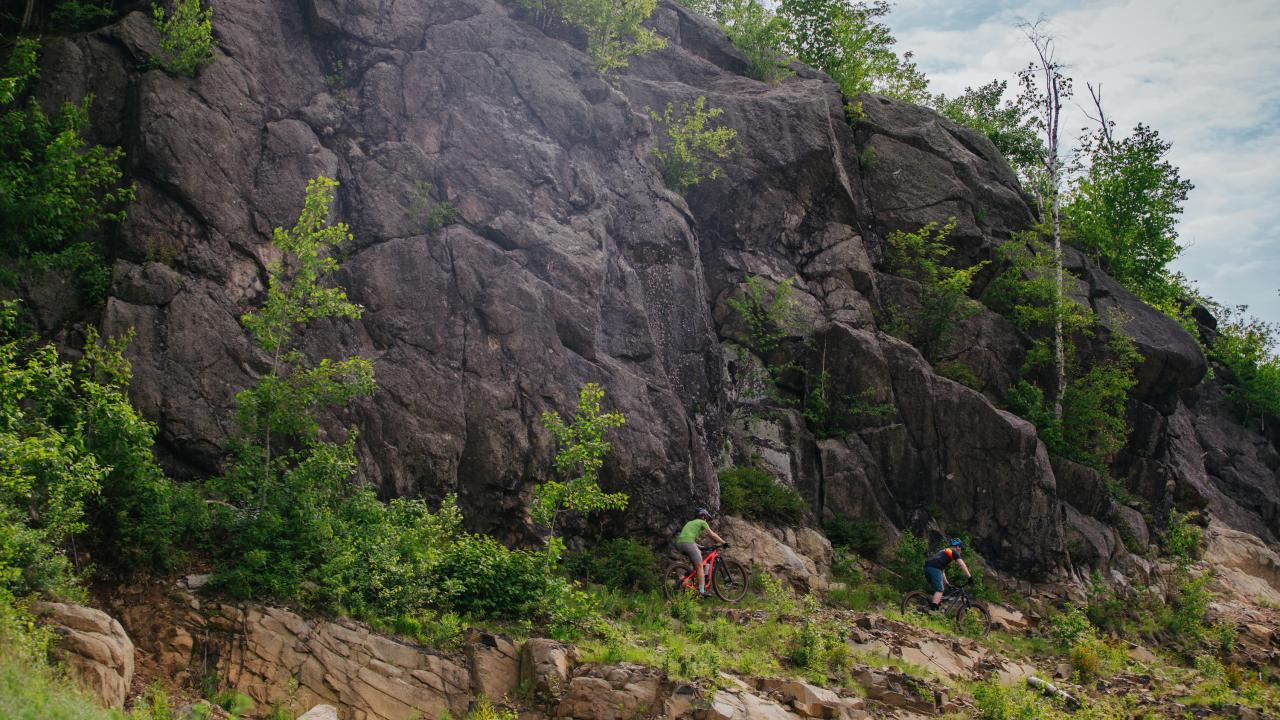 Two mountain bikers riding near rock face in Duluth