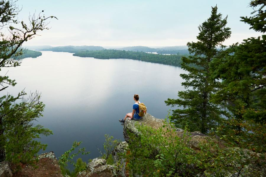 Woman sitting on cliff in Superior National Forest