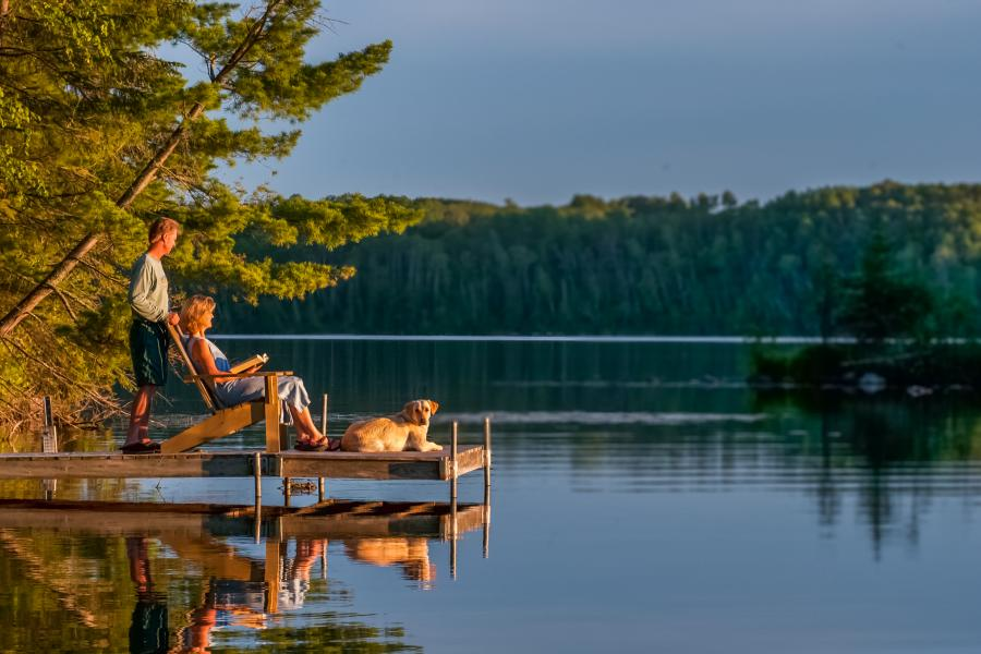 Couple relaxing with dog on dock