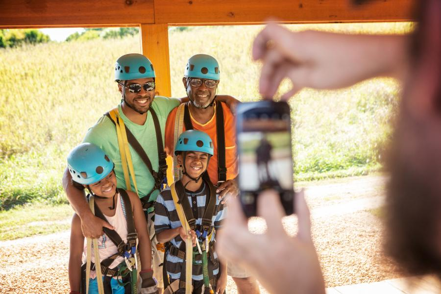 Family poses for photo in zip lining gear