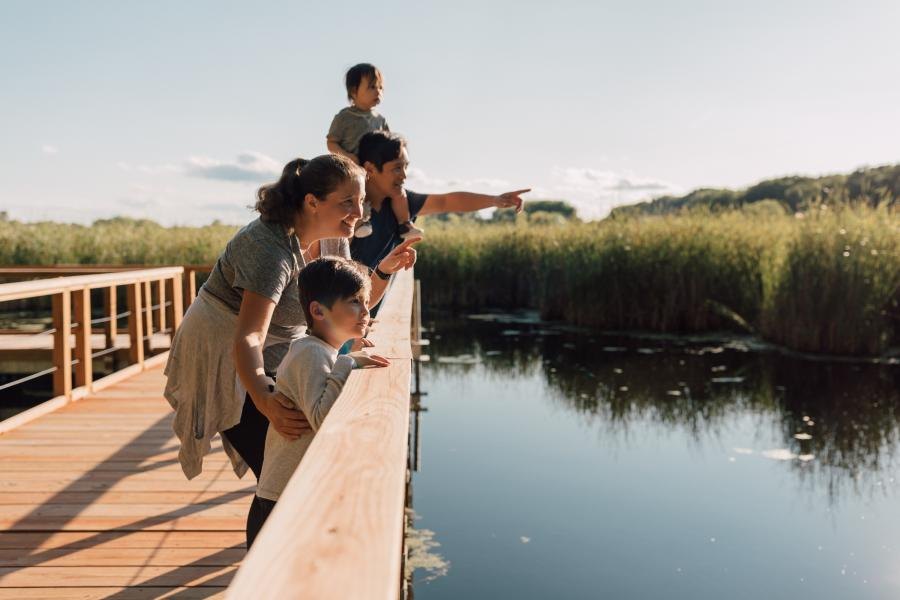 Family takes in the view of Wood Lake Nature Center from a wooden bridge