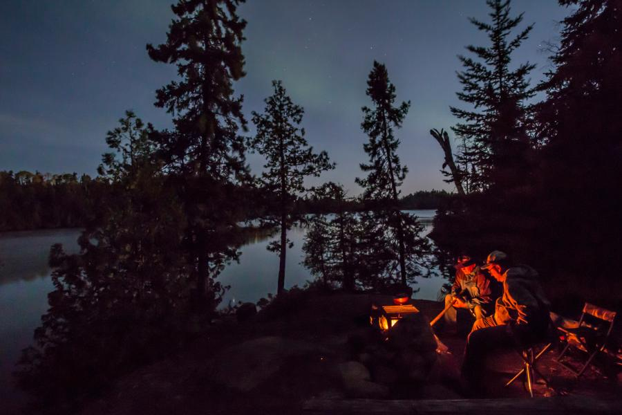 Two people sit around a campfire in the Boundary Waters as the northern lights glimmer in the distance