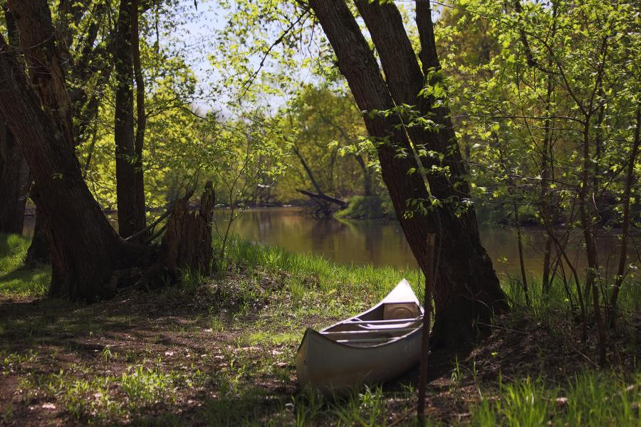 A canoe sits in the shadows onthe bank of the Rum River, Dappled sunlight through the trees as the river lazily drifts by in the background