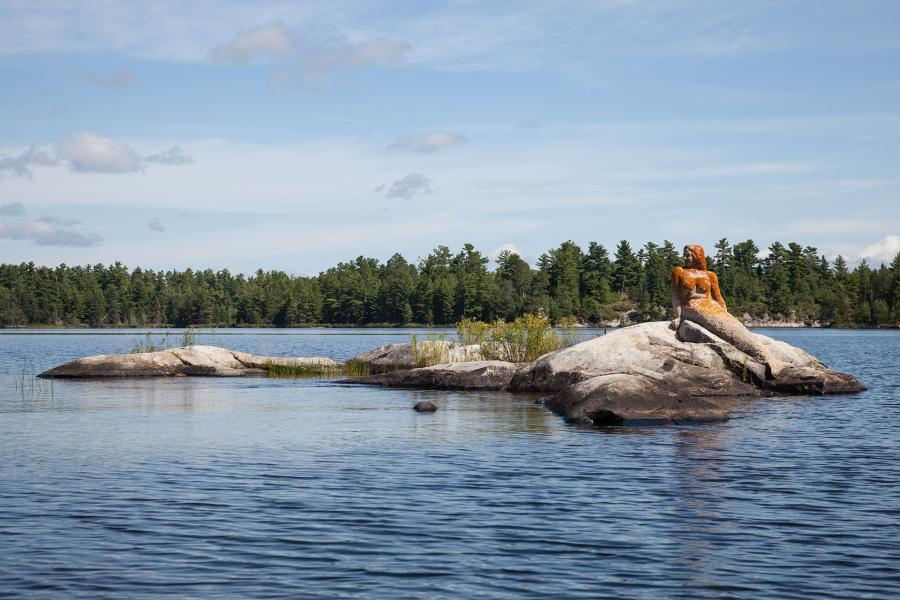A statue of a stone mermaid sits atop a rock formation in the middle of Rainy Lake in Voyeugers National Park