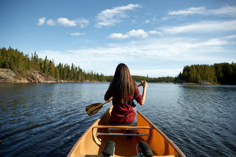 Woman in red shirt canoeing in the Boundary Waters, surrounded by dense forests and clear blue skies