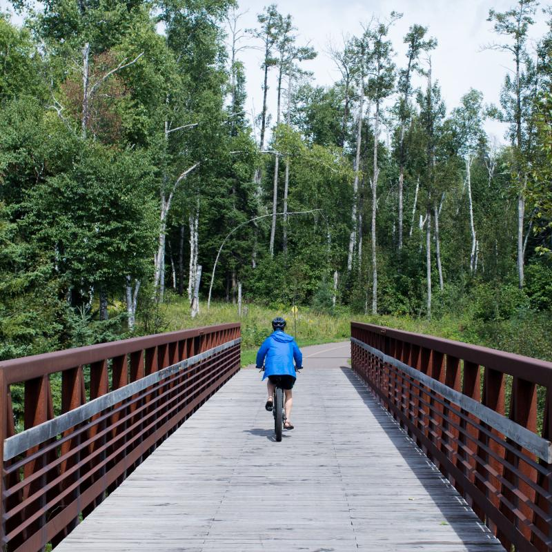 Bicyclist rides across a bridge on the Gitchi-Gami State Trail