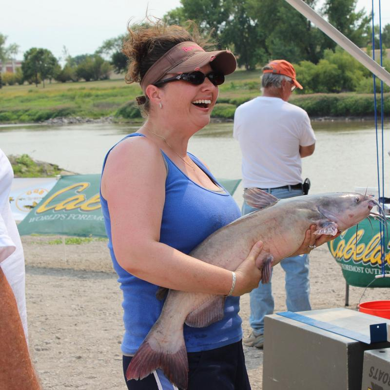 Woman holds a catfish during a Catfish Tournament on the Red River