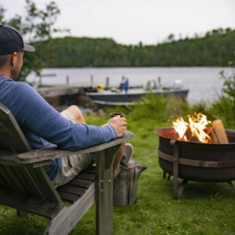 Man with coffee mug at campfire overlooking a lake
