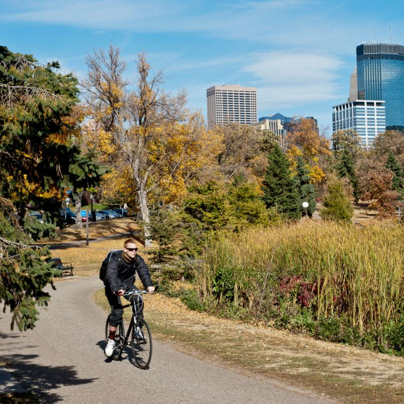 Bicyclist riding through Loring Park with Minneapolis skyline in background