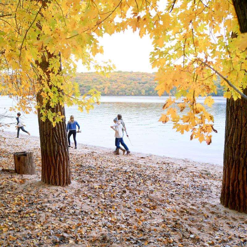 Family walks along river in fall
