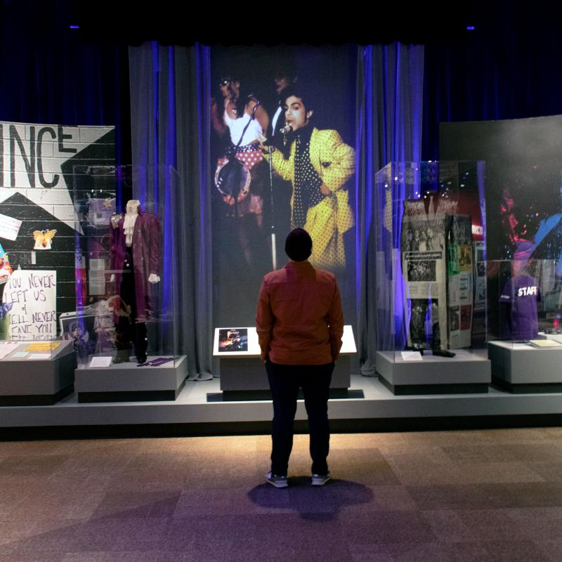 Man stands in front of Prince museum exhibit
