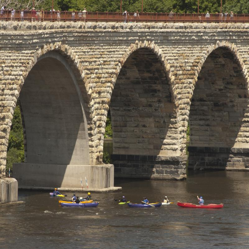 Canoes on the Mississippi River beneath the Stone Arch Bridge