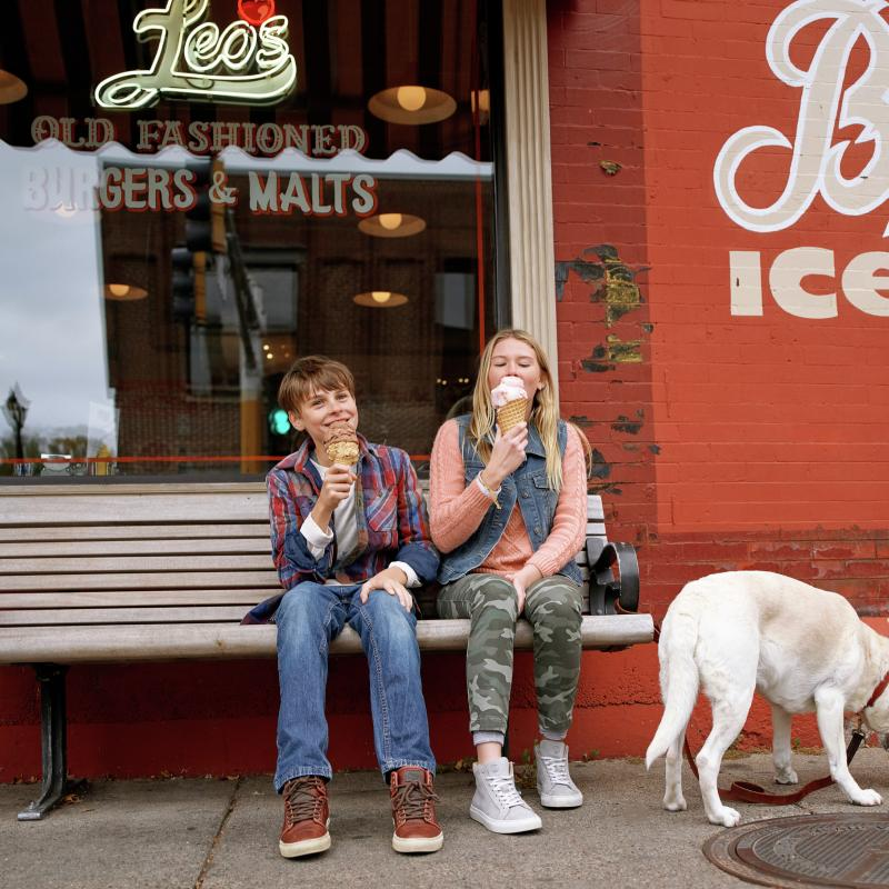 Two kids and dog eating ice cream on bench in Stillwater