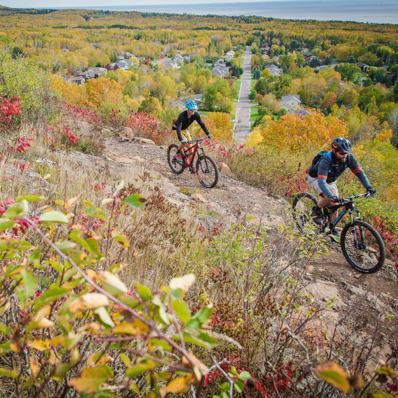 Two mountain bikers on a hill overlooking Duluth in fall