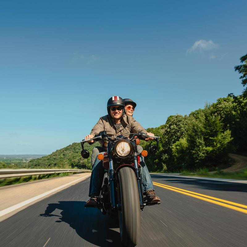 Red wing smiling couple driving motorcycle