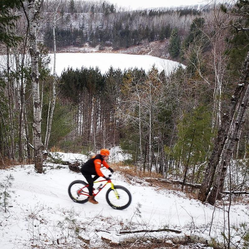 Winter fat biker at Cuyuna in front of mining pit lake