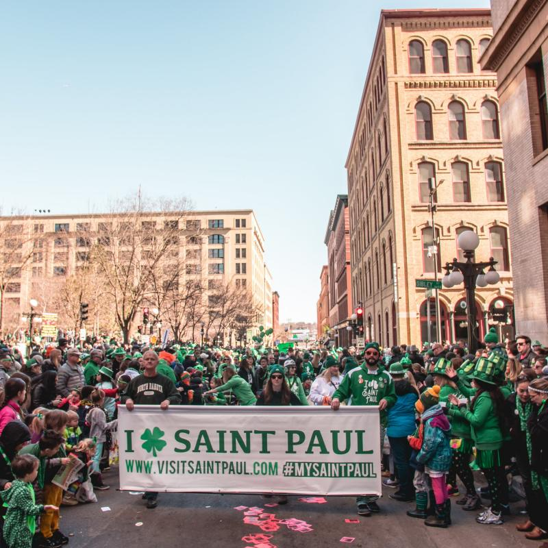 St. Patrick's Day parade-goers holding a Visit Saint Paul banner