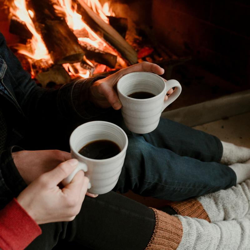 Couple drinking coffee by the fireplace