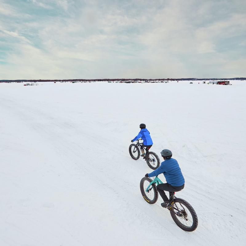 Two people fat biking on a frozen Minnesota lake