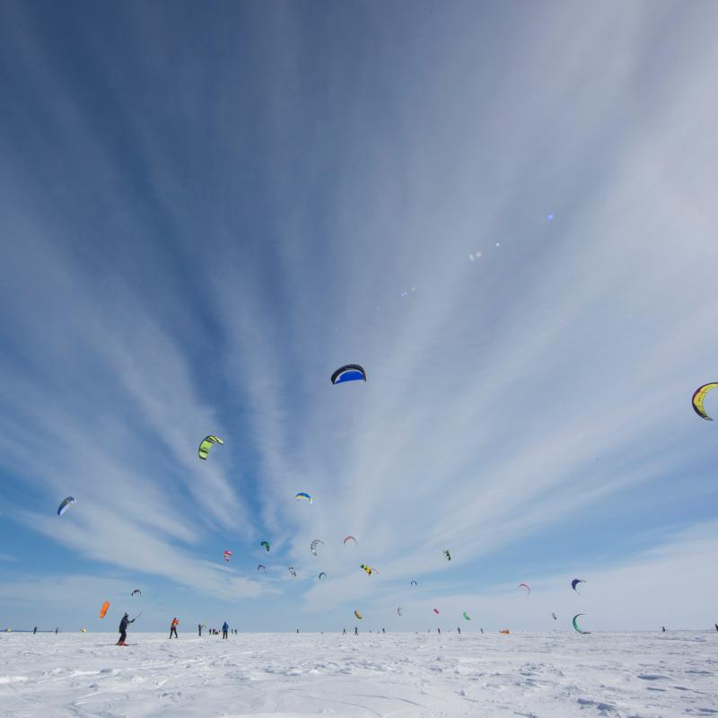 People flying colorful kites on frozen Lake Mille Lacs