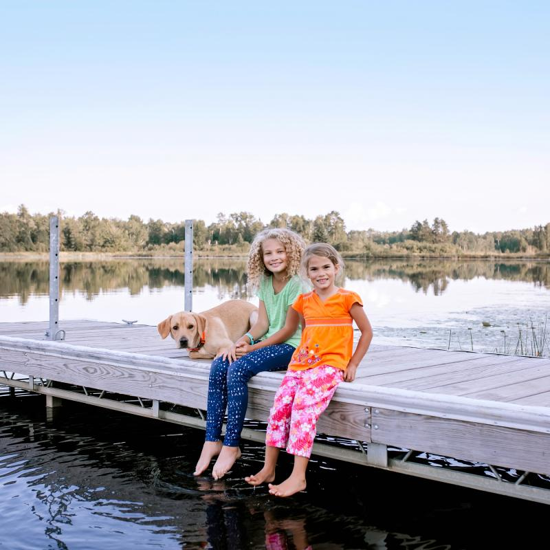 Kids sit with their dog on a dock