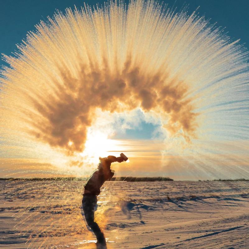 A man throws boiling water into the air during winter, creating a wave of ice crystals