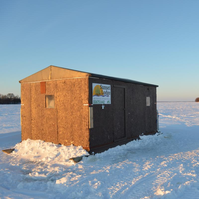 Wooden ice fishing house on Lake of the Woods on a sunny winter day