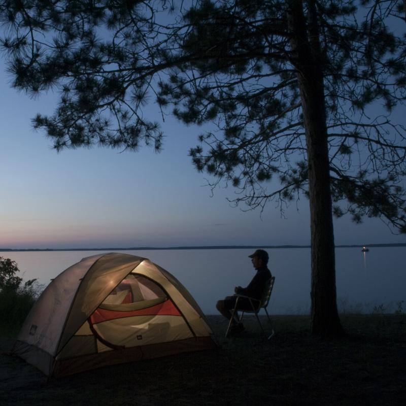 A man sits by a tent near the water at night